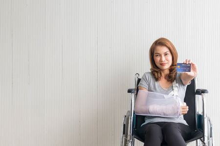 Female patients with broken arms, wheelchair women holding credit cards