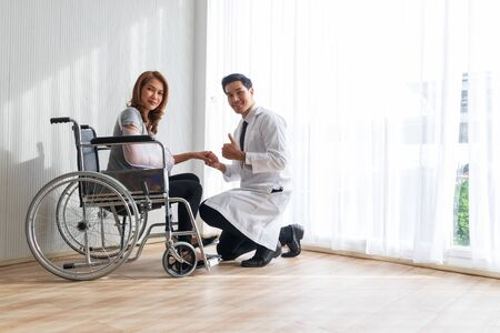 Young doctor encouraged the female patient on the broken arm and wheelchair patient. Stock Photo