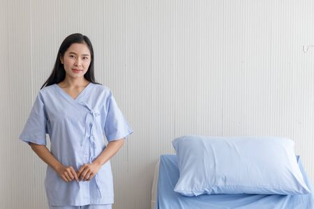 Asian girl patient standing beside bed in hospital