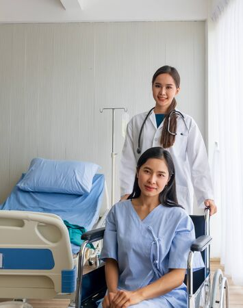 An Asian female doctor cheered on a female patient in a wheelchair in her room.