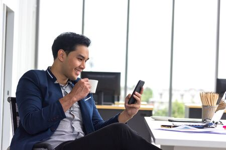 Young Asian businessmen watch smart phones and hold coffee mugs at work. Stock Photo