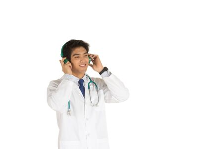 A young Asian doctor with a stethoscope Putting green music headphones to relax on the white background Stock Photo