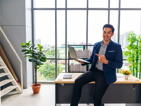 A young Asian businessman with a notebook And smile in the office