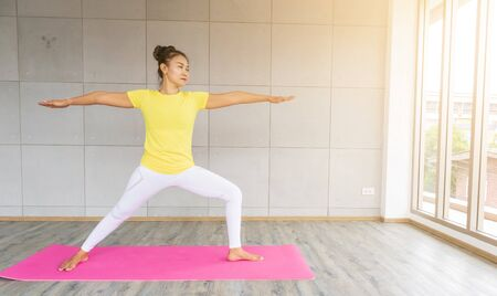 Beautiful asian young woman wearing sportswear practicing yoga in studio Stock Photo