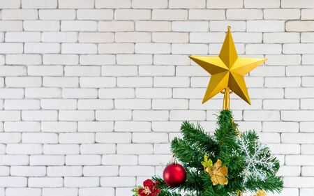 Christmas tree is decorated with the golden star on top, glass ball and glittery golden ball. White wall background. Stock Photo