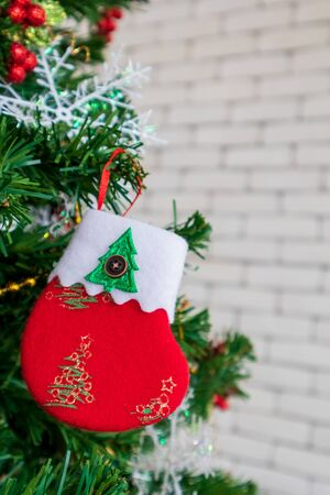 Christmas tree decorated with Red sock on a white wall, copy space. Stock Photo