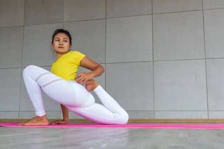 Beautiful asian young woman wearing sportswear practicing yoga in studio,natural light.Concept : yoga poses for beginner.