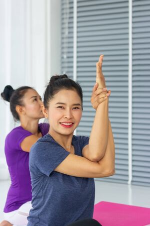 Asian yoga teachers teach students one-on-one in the gym to be healthy and strong.