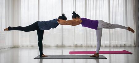 Teacher teach student to do yoga concept. A middle-aged Asian woman is teaching another woman to do yoga in a stretching position, where the teacher comes to catch the right posture.