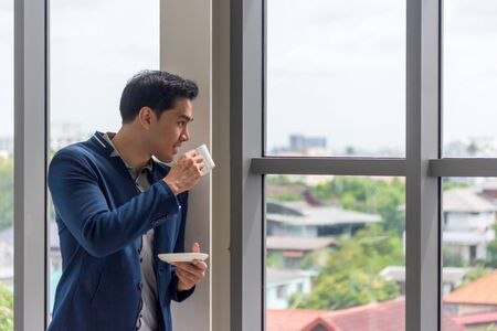 A young Asian businessman drinks coffee in the office window in a comfortable