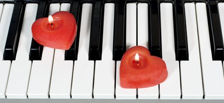 Piano keys with two heart-shaped candles Stock Photo