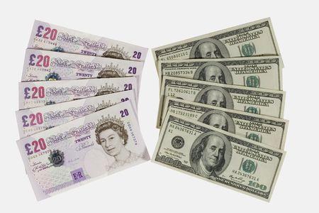 Twenty-pound notes and one-hundred dollar bills (isolated on white)