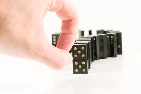 Human fingers ready to push a row of black dominoes (on white) Stock Photo
