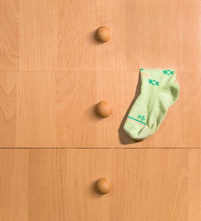 Childs sock hanging from a chest of drawers