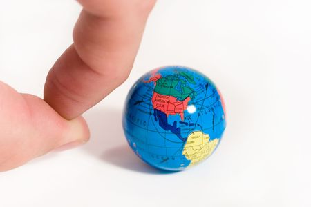 Human fingers ready to push a small globe (symbolizing our planet) Stock Photo