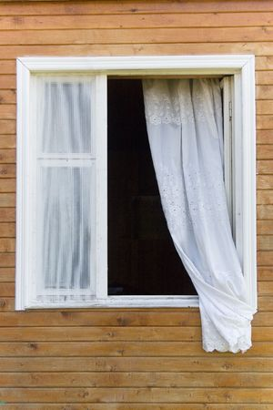 Old traditional country-style window in a wooden house (with a white curtain)