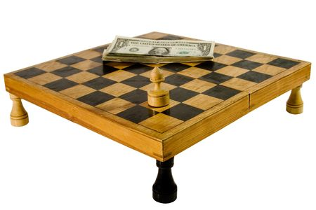 Old wooden chessboard resting upon the rooks, with a pawn and pile of dollars (isolated on white) photo