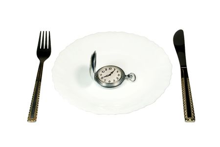 """consuming: Dining table and antique pocket watch on a white plate (""""eating up time"""" concept)"""