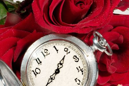 Antique pocket watch on red rose buds and petals photo