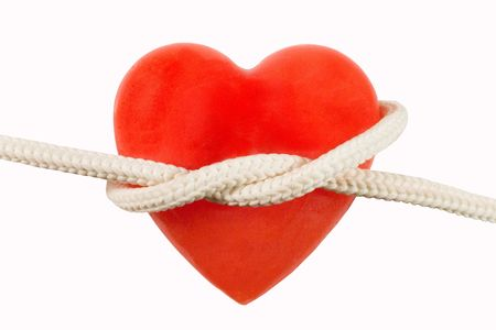 enslave: Red heart-shaped candle (symbolizing a human heart) and a rope Stock Photo