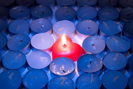 blown: Burning red heart-shaped candle among rows of blown out candles Stock Photo