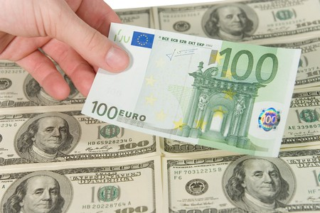 onehundred: Hand holding a one-hundred euro bill (against the background of one-hundred dollar bills) Stock Photo