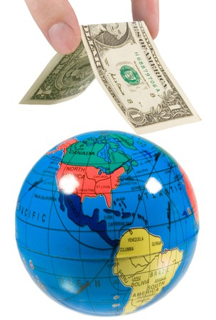 Hand putting a dollar roof on the globe (isolated on white) photo