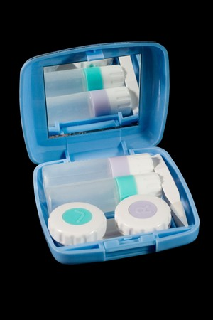 Set of contact lens cases, bottles and tweezers (isolated on black) photo