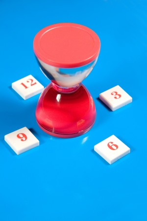 Red liquid hourglass and digits symbolizing hours (on a bright blue background) Stock Photo - 4300768
