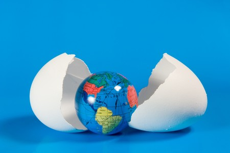 Small globe in broken eggshell (on a blue background) Stock Photo - 4300763