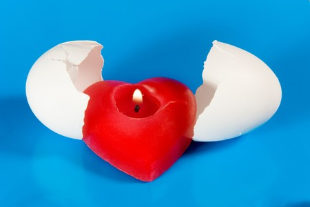 Burning red heart-shaped candle in broken eggshell (symbolizing the Birth of Love) photo