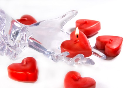 Red heart shaped candles and glass or ice hand holding a burning candle (Fragility of Love concept) photo