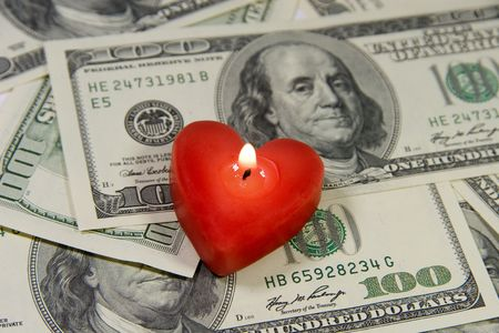 Red heart-shaped candle on a pile of US dollars (Love for Money concept) photo