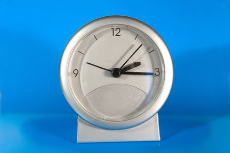 silvery: Simple gray desk clock (on a bright blue background) Stock Photo