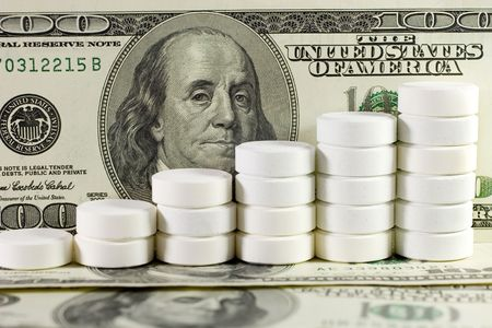 Pile of white pills (in the form of a staircase) against the background of US dollars Stock Photo