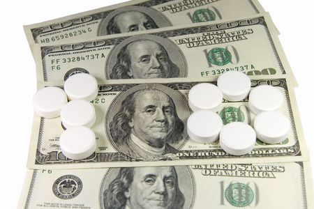 White pills forming �one hundred� on a bunch of US dollars (isolated on white) photo