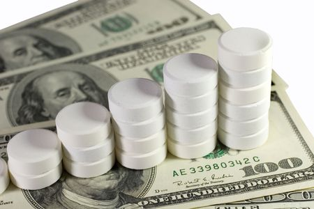 Pile of white pills (in the form of a staircase) on US dollars photo
