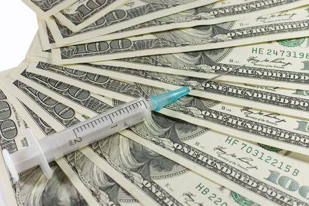 Closeup of a syringe on US dollars (isolated on white) photo