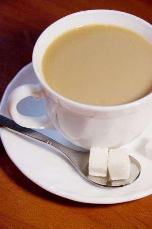 White coffee cup with freshly made white coffee and two cubes of sugar (on a wooden table) Stock Photo