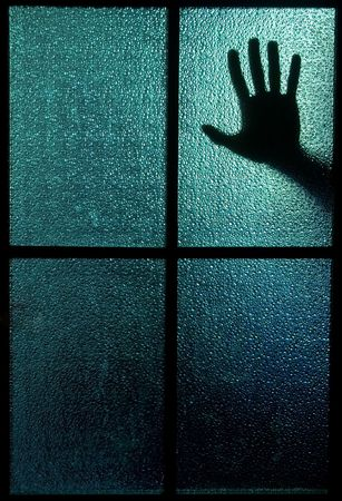 Silhouette of a hand behind a window or glass door (symbolizing horror or fear) photo