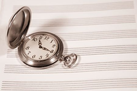 Pocket watch on a sheet of music paper (in sepia, retro style) Stock Photo