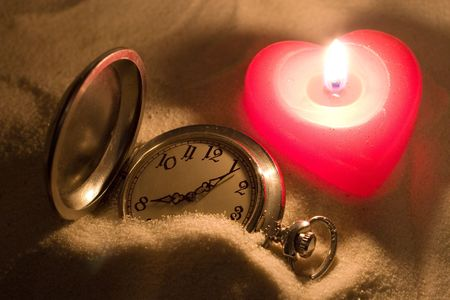Antique watch covered with sand and a red heart-shaped candle Stock Photo