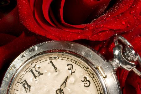 timekeeping: Beautiful red rose with drops of water and antique pocket watch Stock Photo