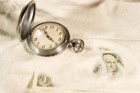 Antique pocket watch and US dollar bill covered with sand Stock Photo - 5600934