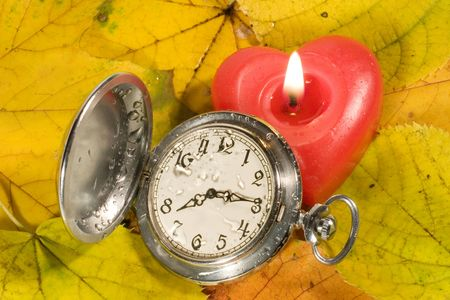 withering: Antique watch with raindrops on the face and red heart-shaped candle against the background of autumn leaves