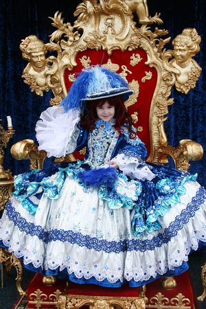 Smiling little girl wearing an antique princess dress (sitting on a princess throne and holding a blue fan)