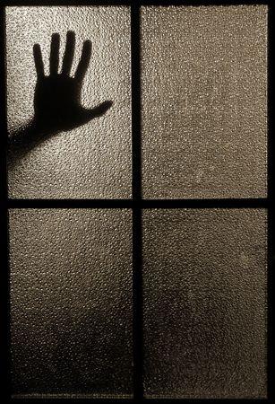 Leicht verschwommen Silhouette einer Hand hinter einem Fenster oder Glastüren (symbolisiert Schrecken oder Furcht) Standard-Bild