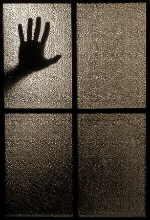 gloom: Slightly blurred silhouette of a hand behind a window or glass door (symbolizing horror or fear) Stock Photo