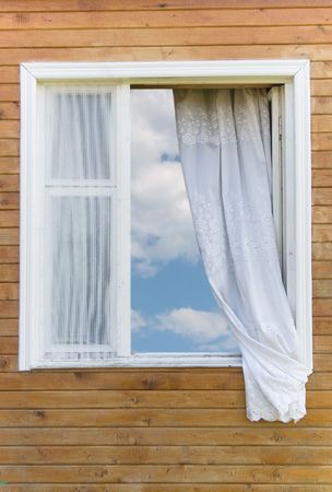 Old traditional country-style window in a wooden house (with the blue sky and white clouds in the window) photo