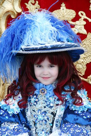 Smiling little girl wearing an antique princess dress (sitting on a princess throne) photo